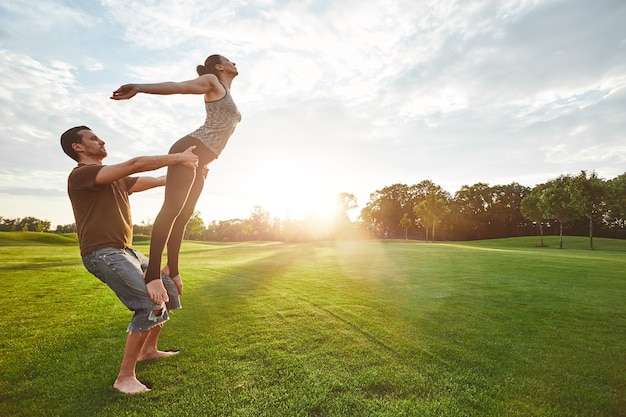 Pratique du vol de deux personnes pratiquant le yoga acro dans la nature par une matinée ensoleillée