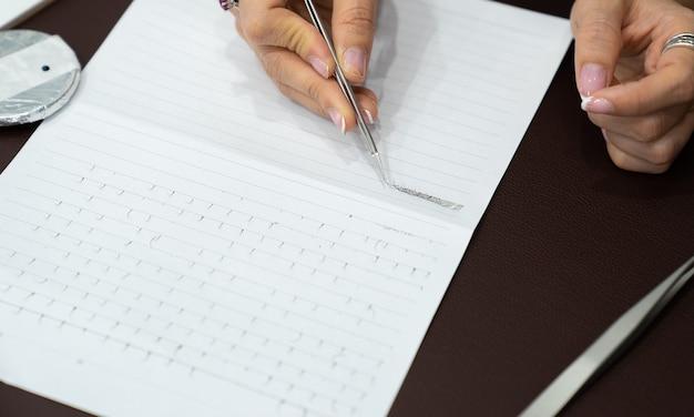 Pratique de la main et entraînement de l'extension des cils sur papier en classe, travail avec twizzers