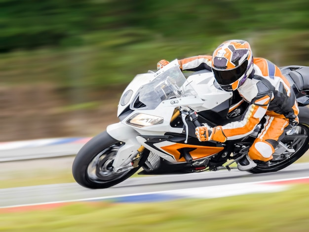 La pratique de la moto se penchant dans un virage rapide sur la bonne voie