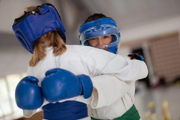 Pratiquer avec une fille. garçon aux yeux noirs portant un casque et des gants pratiquant avec une fille portant un kimono blanc