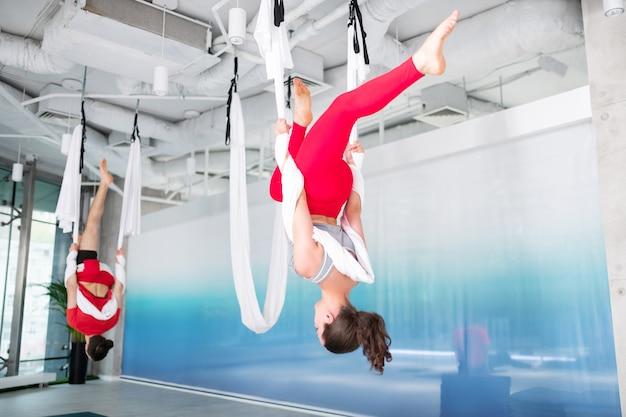 Pratiquer le yoga aérien. femme mince et en forme aux cheveux noirs en leggings rouges pratiquant le yoga aérien