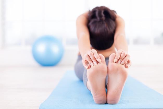 Pratiquer le yoga. belle jeune femme qui s'étend sur un tapis de yoga