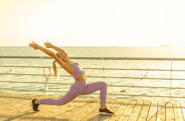 Pratiquer le yoga. entraînement au lever du soleil. jeune femme mince faisant des exercices d'asana sur la plage. concept de mode de vie sain
