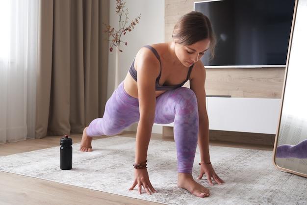 Pratiquer le yoga à la maison dans le concept de sport et de remise en forme de salon