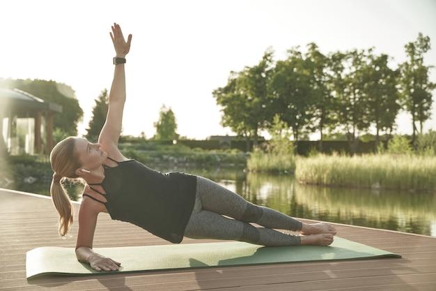 Pratiquer le yoga tôt le matin sur toute la longueur d'une belle jeune femme en tenue de sport