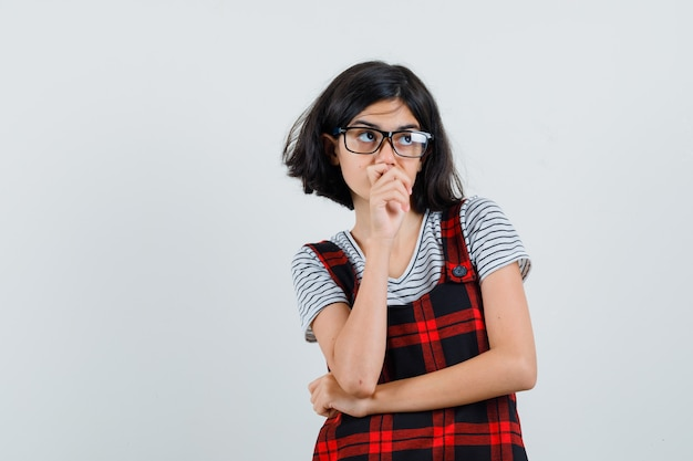 Pré-adolescente en t-shirt, combinaison, lunettes pensant et regardant pensif