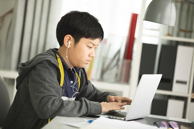 Les pré-adolescents asiatiques font vos devoirs avec un ordinateur portable.