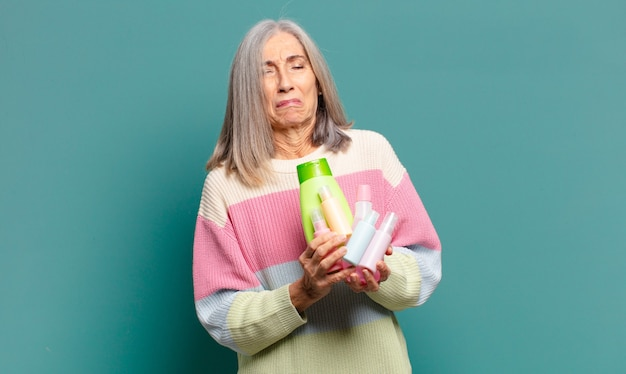 Pré-femme aux cheveux gris avec des produits de soins de la peau