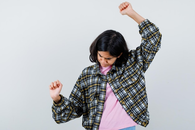 Préadolescente en chemise, veste montrant le geste du gagnant avec les mains en l'air, vue de face.