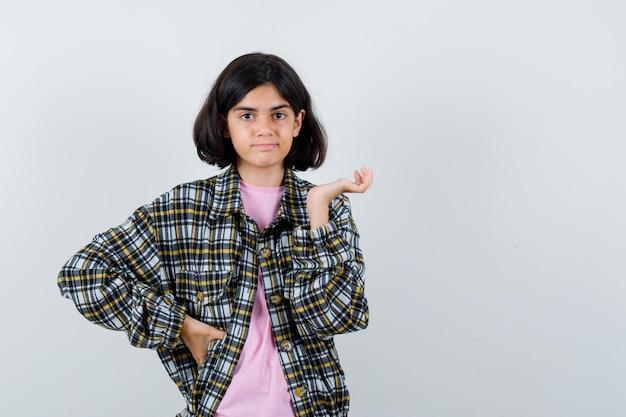 Préadolescente en chemise, veste montrant quelque chose à gauche et l'air mécontent, vue de face.