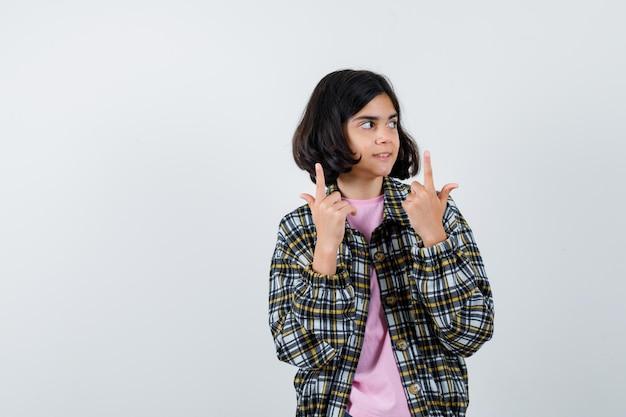 Préadolescente en chemise, veste pointant vers le haut, vue de face.