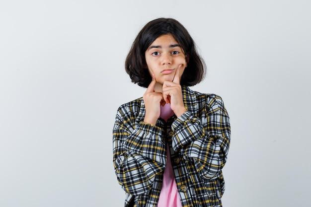 Préadolescente en chemise, veste serrant ses joues, vue de face.