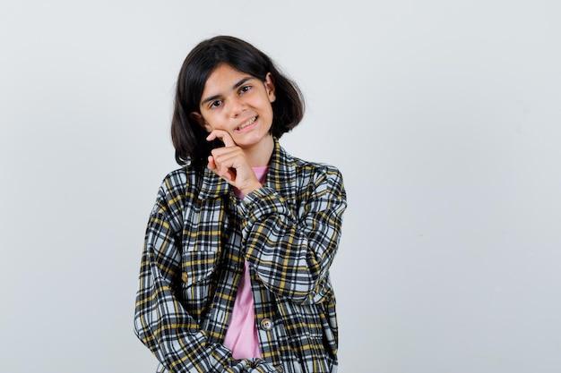 Préadolescente en chemise, veste tenant la main sur la joue, vue de face.
