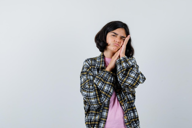Préadolescente faisant un geste d'oreiller en chemise, veste et semblant endormie, vue de face.