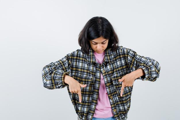 Préadolescente pointant vers le bas en chemise, vue de face de la veste.