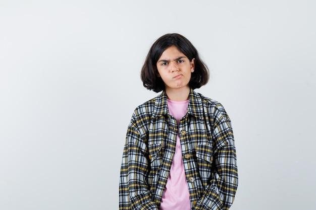 Préadolescente regardant la caméra en chemise, veste et l'air nerveux, vue de face.