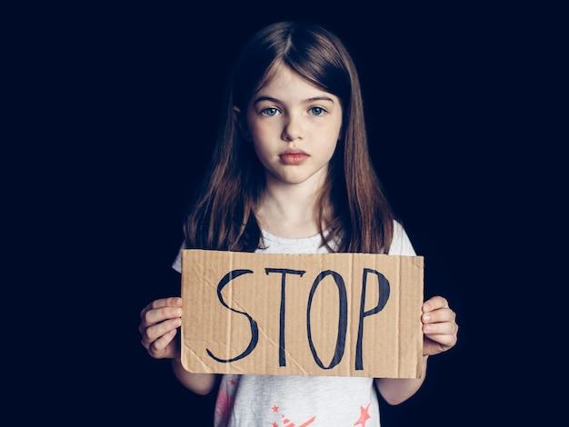 Préadolescente tenant un panneau d'arrêt, concept de problèmes, émotions négatives, dépendance des enfants et adolescents