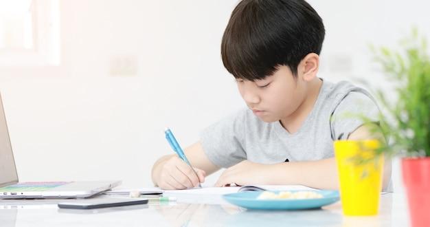 Les préadolescents asiatiques font vos devoirs avec une tablette.