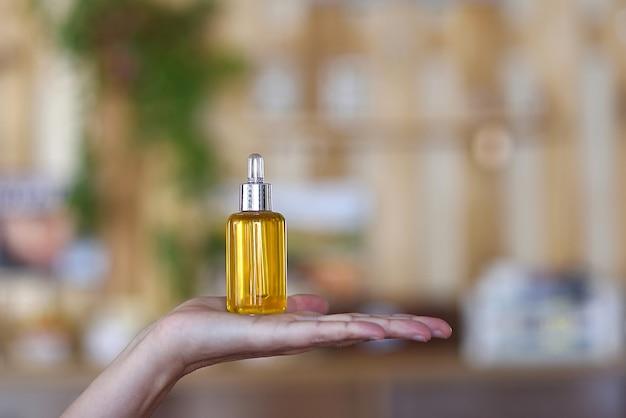 Précieuse bouteille de sérum d'huile médicinale dans la main d'une femme