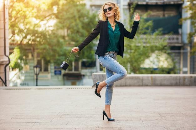 Preety femme élégante marchant dans la rue en jeans bleu portant veste et chemisier vert, accessoires de mode, style élégant, tendances de la mode du printemps