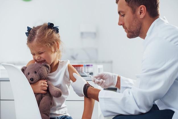 Prélèvement de sang. une petite fille avec son ours en peluche est à la clinique avec un médecin.