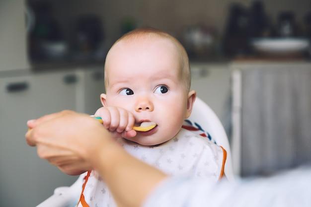 Premier aliment solide du bébé mère nourrissant le petit enfant avec une cuillère de purée routine quotidienne nourriture avec les doigts