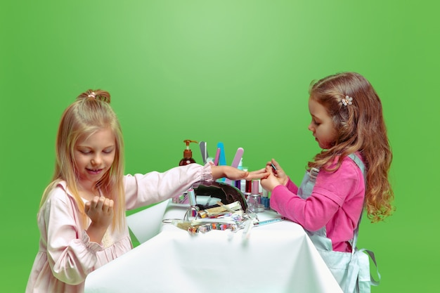 Premier client. petite fille rêvant de la profession d'artiste des ongles. enfance, planification, éducation, concept de rêve. veut devenir un employé à succès dans l'industrie de la mode et du style, artiste de la manucure.