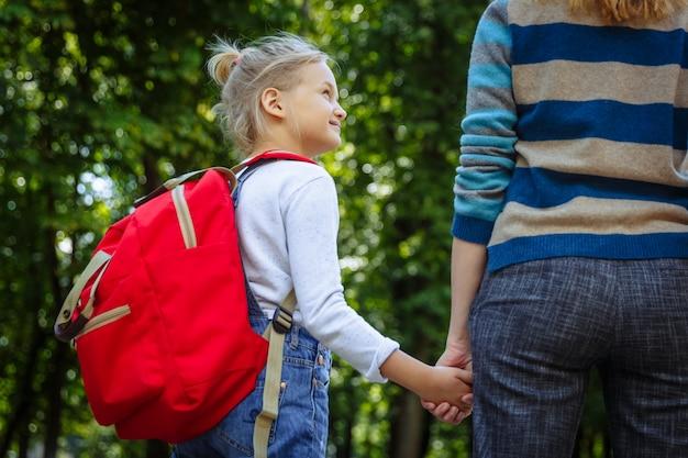 Premier jour à l'école. femme et fille avec sac à dos rouge derrière le dos. début des cours. premier jour d'automne. retour au concept de l'école.