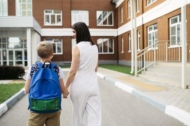 Premier jour à l'école. la mère dirige un écolier en première année. concept de retour à l'école