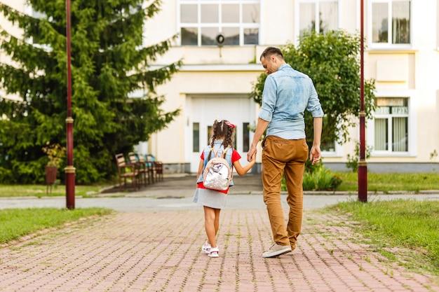 Premier jour à l'école. père mène une petite écolière enfant