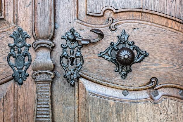 Premier plan de la vieille porte en bois avec poignée en fer. vieille poignée de porte rouillée sur porte en bois.