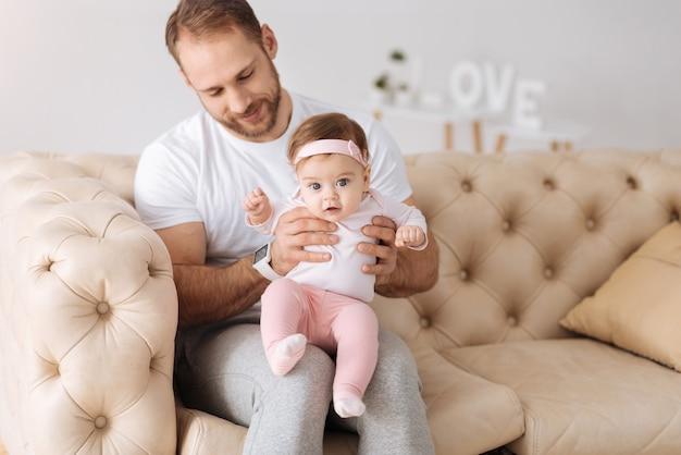 La première année de vie. enthousiaste homme impliqué attentif assis sur le canapé à la maison et étreignant son enfant tout en exprimant des émotions tendres et au repos