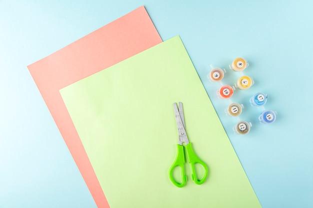 Première étape de la fabrication d'un papillon en papier origami avec du papier vert, des ciseaux sur fond bleu