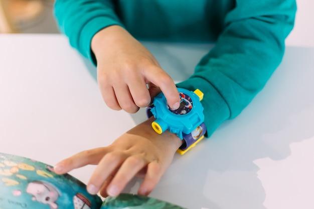 Première montre pour petit garçon apprenant à déterminer l'heure par l'horloge