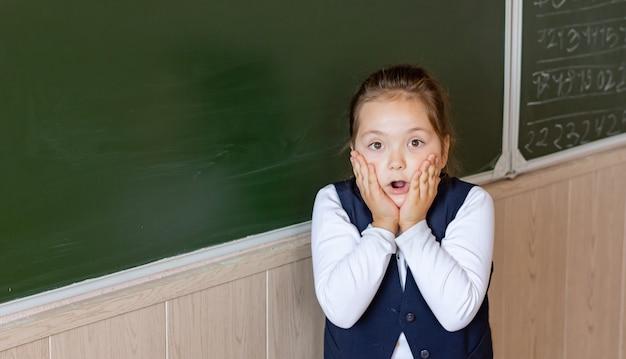 Une première niveleuse se tient au tableau et a très peur. retour à l'école.