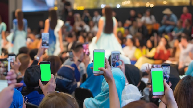 Première rangée d'invités vip de l'audience filmant le défilé vdo avec un téléphone intelligent