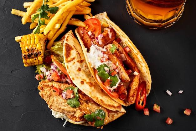 Première tortilla de maïs avec filet de poulet grillé deuxième avec filet de poisson sauce frites et bière ...
