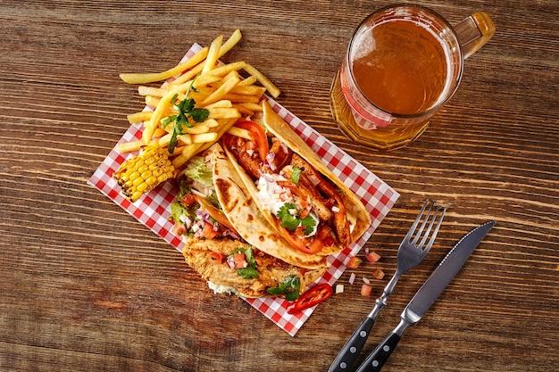 Première tortilla de maïs avec filet de poulet grillé deuxième avec sauce au filet de poisson et bière sur onglet en bois...