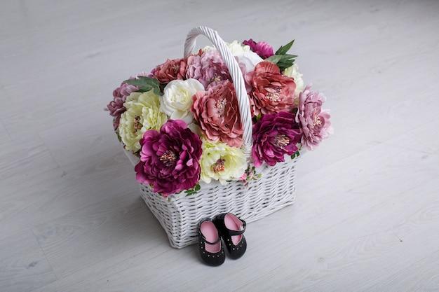 Premières chaussures pour petite princesse isolée sur un mur clair avec un espace pour le texte. chaussons bébé en cuir verni noir avec fleurs en osier panier. chaussures élégantes pour fille nouveau-née pour les premiers pas se bouchent.