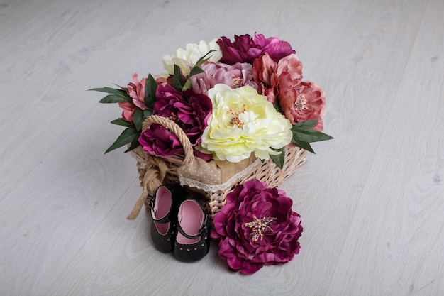 Premières chaussures pour petite princesse isolée sur table lumineuse avec un espace pour le texte. chaussons bébé en cuir verni noir avec fleurs en osier panier. chaussures élégantes pour fille nouveau-née pour les premiers pas se bouchent.