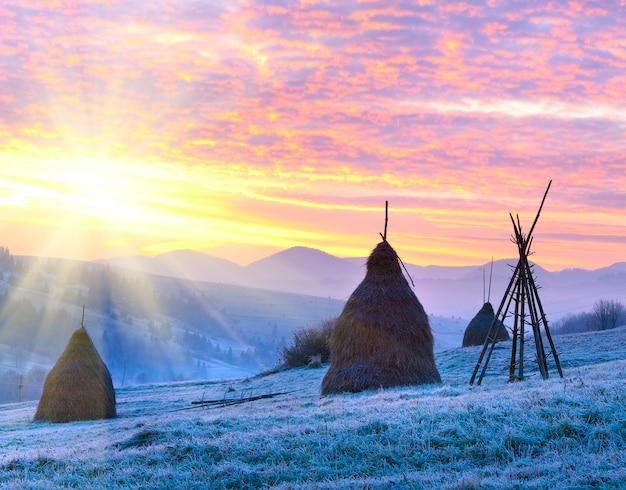 Premières gelées d'automne sur les pâturages avec des meules de foin et un lever de soleil majestueux dans le village des montagnes