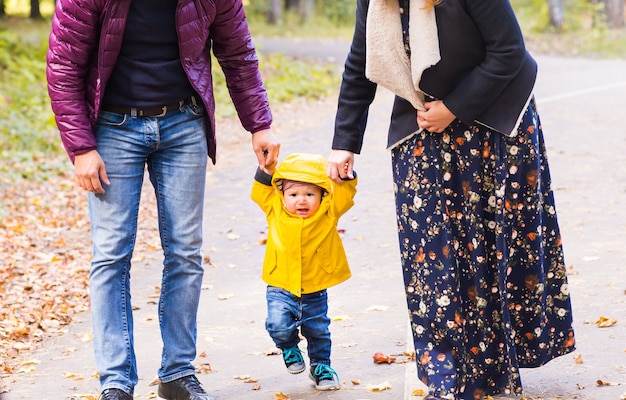 Premiers pas de petit garçon avec la mère et le père