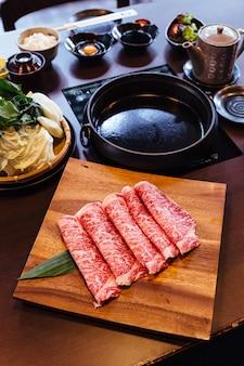 Premium rare slices wagyu a5 boeuf à texture marbrée élevée sur une assiette en bois carrée.