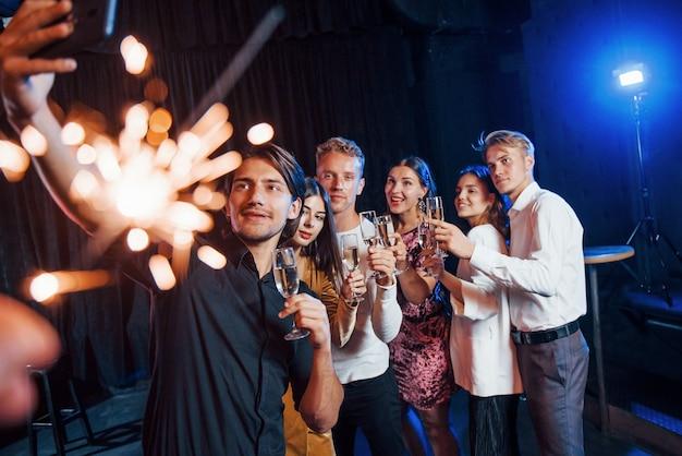 Prend un selfie. groupe d'amis joyeux célébrant le nouvel an à l'intérieur avec des boissons à la main.