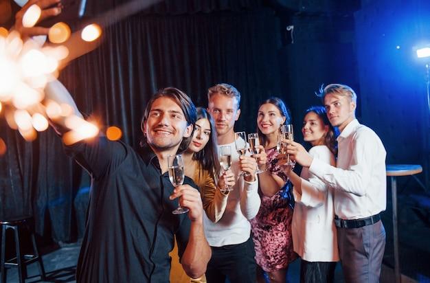 Prend Un Selfie. Groupe D'amis Joyeux Célébrant Le Nouvel An à L'intérieur Avec Des Boissons à La Main. Photo Premium