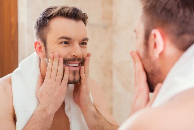 Prendre bien soin de son visage. beau jeune homme touchant son visage et souriant tout en se tenant devant le miroir