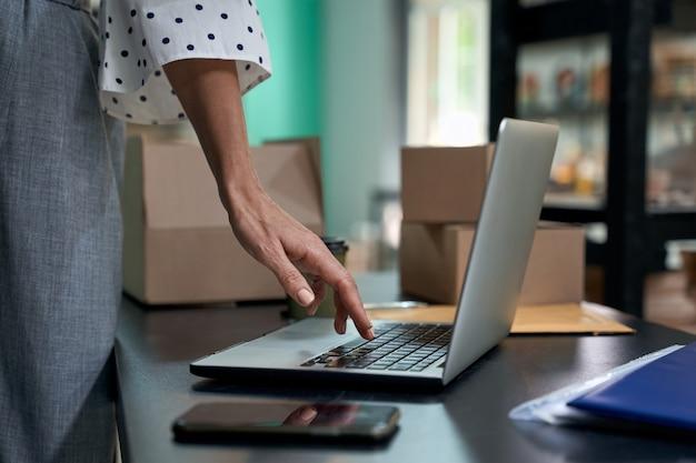 Prendre des commandes en ligne photo recadrée d'une femme propriétaire d'entreprise utilisant un ordinateur portable en position debout