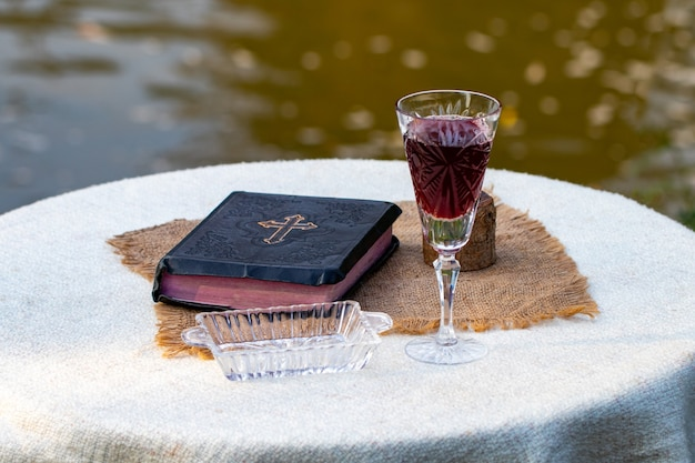 Prendre la communion. tasse de verre avec du vin rouge, du pain et de la sainte bible sur une table en bois en gros plan.