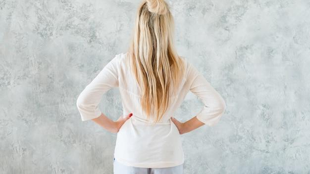 Prendre le concept de décision. femme blonde mains sur la vue arrière des hanches.