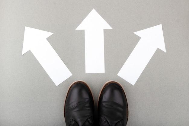 Prendre une décision dans la direction à suivre marcher sur le panneau directionnel sur la route asphaltée